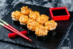 Baked sushi roll on black stone serve stock photos
