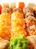 Baked sushi rolls with orange and red roe closeup Royalty Free Stock Photography