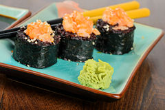Baked sushi rolls served on blue plate Stock Photography