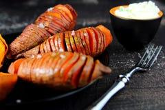 Baked sweet potato with salt. On a black dish Royalty Free Stock Photos