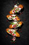 Baked sweet potatoes with garlic mint yogurt sauce sprinkled with pomegranate seeds and fresh mint leaves on a black background, t stock image