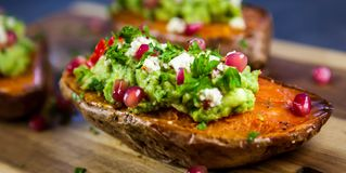 Baked sweet potatoes served with guacamole, feta cheese and pomegranate. Healthy food - Baked sweet potatoes served with guacamole, feta cheese and pomegranate royalty free stock photos