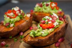 Baked sweet potatoes served with guacamole, feta cheese and pomegranate. Healthy food - Baked sweet potatoes served with guacamole, feta cheese and pomegranate royalty free stock images