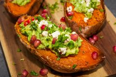 Baked sweet potatoes served with guacamole, feta cheese and pomegranate. Healthy food - Baked sweet potatoes served with guacamole, feta cheese and pomegranate royalty free stock photography