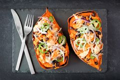 Baked, stuffed sweet potatoes, above view on slate Stock Photos