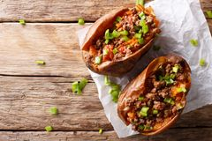 Baked sweet potatoes stuffed with ground beef with tomatoes and. Onions on paper on a table. Horizontal top view from above Royalty Free Stock Photos