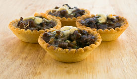 Baked tartlets with mushrooms and cheese on a wooden table. Four baked tartlets with mushrooms and cheese on a wooden table Stock Photos