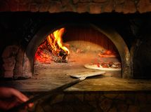 Baked tasty margherita pizza getting out of the oven Stock Image