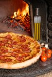 Baked tasty pizza with salami and bacon Royalty Free Stock Photography