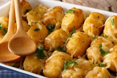 Baked Tater Tots with cheese and herbs close up in a dish baking. Dish on the table. horizontal Royalty Free Stock Image