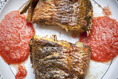 Baked tilapia served with red pepper sauce Royalty Free Stock Photos