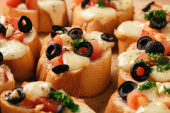 Baked toasts with mozarella, tomatoes, olives and garlic. Royalty Free Stock Photography