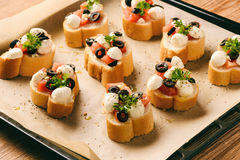 Baked toasts with mozarella, tomatoes, olives and garlic. Royalty Free Stock Photos