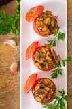 Baked tomatoes stuffed with eggplant and mushrooms. On table Royalty Free Stock Photos