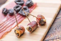 Baked torkade plommoner som fylldes med ost, och bacon rullade, mellanmålet eller aptitretaren royaltyfri bild