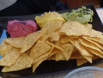Baked tortilla chips served with a trio of vegetable dips royalty free stock images