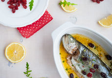 Baked trout fish with cherries, lemon and salad rocket Royalty Free Stock Images