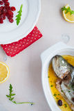Baked trout fish with cherries, lemon and salad rocket Stock Photos