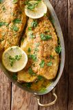 Baked trout fish with garlic lemon butter sauce, parsley closeup. In a copper frying pan on a table. Vertical top view from above royalty free stock photo