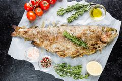 Baked trout fish. With salt, lemon and rosemary on paper over black background stock photo