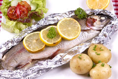 Baked Trout. A baked trout with new potatoes and salad Stock Image