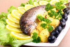 Baked trout with potatoes, black olives, salad and lemon Royalty Free Stock Image