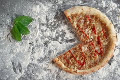 Baked tuna pizza and green leaves on dark background with scattered white flour. Directly above photo stock image