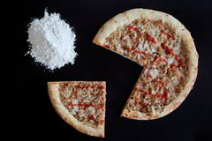Baked tuna pizza and pile of flour on black background. Directly above photo stock photos