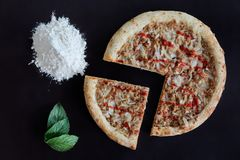 Baked tuna pizza, pile of flour and green leaves on black background. Directly above photo royalty free stock photo