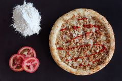 Tuna pizza, pile of flour and slices of tomato on black background. Baked tuna pizza, pile of flour and slices of tomato on black background stock images