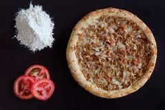 Baked tuna pizza, pile of flour and slices of tomato on black background. Directly above photo stock images