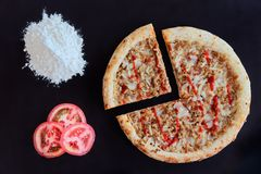 Baked tuna pizza, pile of flour and slices of tomato on black background. Directly above photo royalty free stock photo