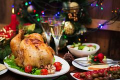 Baked turkey or chicken. The Christmas table is served with a turkey, decorated with bright tinsel and candles. Fried chicken, table. Christmas dinner Royalty Free Stock Images