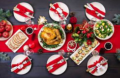 The Christmas table is served with a turkey, decorated with bright tinsel. Baked turkey. Christmas dinner. The Christmas table is served with a turkey, decorated royalty free stock photos