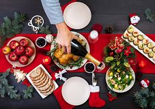 Baked turkey. Christmas dinner. The Christmas table is served with a turkey, decorated with bright tinsel and candles. Fried chicken, table. Family dinner. Top royalty free stock image