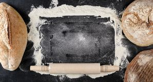 Baked various loaves of bread and rolling pin. On a black background, empty space in the middle, top view stock photo