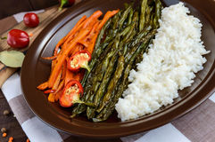 Baked vegetables (asparagus beans and carrot), boiled rice and rye croutons. Vegetarian cuisine. Close up Stock Photo