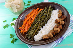 Baked vegetables (asparagus beans and carrot), boiled rice and rye croutons. Vegetarian cuisine. Close up Stock Photos