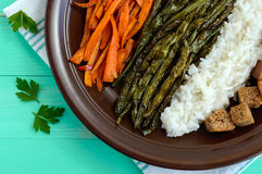 Baked vegetables (asparagus beans and carrot), boiled rice and rye croutons. Vegetarian cuisine. Close up Stock Photography