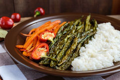 Baked vegetables (asparagus beans and carrot), boiled rice and rye croutons. Vegetarian cuisine. Close up Stock Images