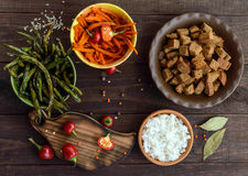 Baked vegetables (asparagus beans and carrot), boiled rice and rye croutons. Vegetarian cuisine. The top view Stock Image