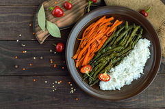 Baked vegetables (asparagus beans and carrot), boiled rice and rye croutons. Vegetarian cuisine. The top view Royalty Free Stock Photo