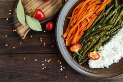 Baked vegetables (asparagus beans and carrot), boiled rice and rye croutons. Vegetarian cuisine. The top view Stock Photography