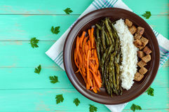 Baked vegetables (asparagus beans and carrot), boiled rice and rye croutons. Vegetarian cuisine. The top view Stock Photo