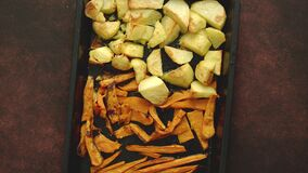 Baked vegetables. Potatoes, carrot and sweet potatoes on metal tray.