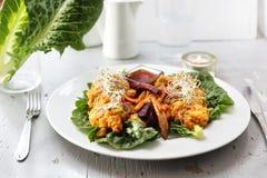 Baked vegetables, sweet potato, potato, celery, carrot, beet served with vegetable stew on iceberg lettuce royalty free stock images