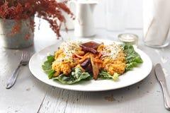 Baked vegetables, sweet potato, potato, celery, carrot, beet served with vegetable stew on iceberg lettuce stock image