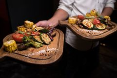 Two portions baked vegetables on a wooden tray royalty free stock image