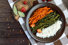 Baked vegetables (asparagus beans and carrot), boiled rice and rye croutons. Stock Photography