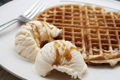 Baked waffle with ice-cream. Freshly baked waffle with two scoops of vanilla ice-cream covered with syrup, served on a white plate Royalty Free Stock Photos